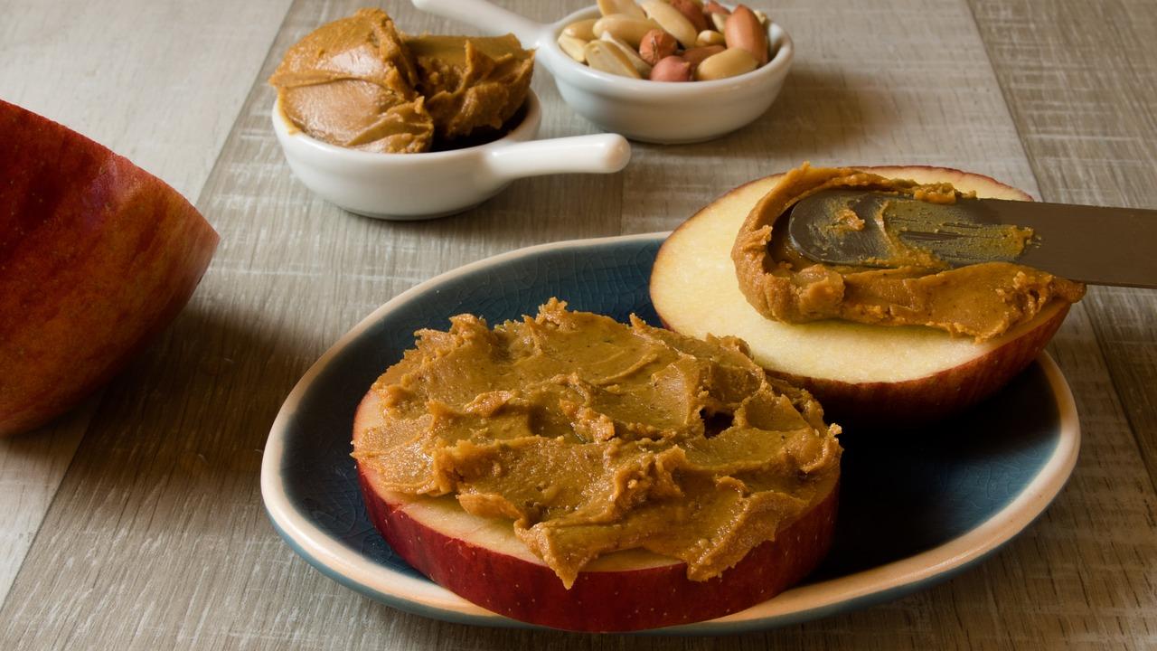 Peanut butter slathered on an apple slice