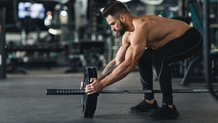 lifter adding weight to barbell