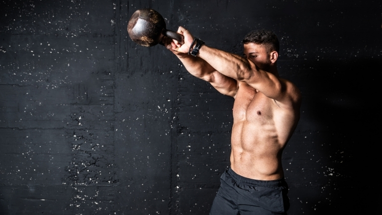 man swinging kettlebell